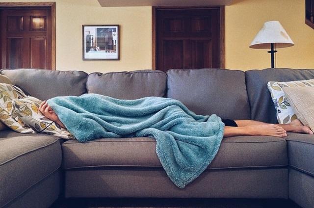 Człowiek leżący pod kocem na kanapie
