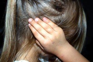 Dziewczynka zasłania uszy
