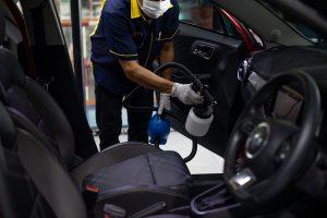 Pracownik myjni oczyscza wnętrze auta